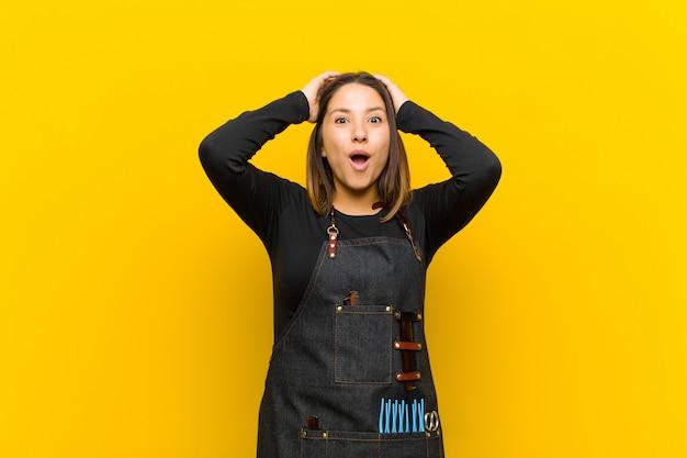 Friseurfrau, die aufgeregt und überrascht, mit beiden händen auf dem kopf mit offenem mund aussieht und sich wie ein glücklicher gewinner fühlt