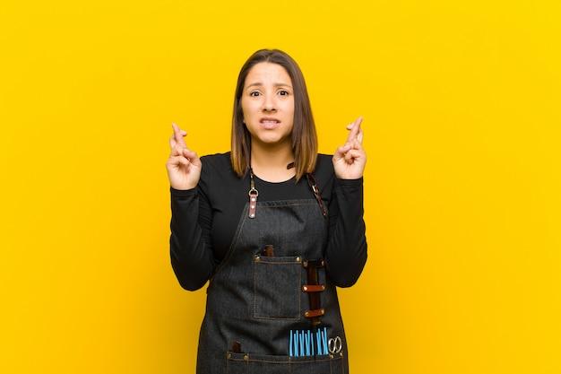 Friseurfrau, die besorgt finger kreuzt und auf gutes glück mit einem besorgten blick gegen orange wand hofft