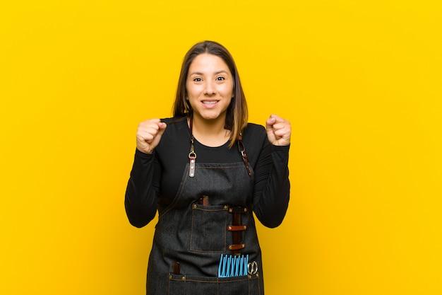 Friseurfrau, die entsetzt, aufgeregt und glücklich sich fühlt, erfolg lacht und feiert und wow sagt! gegen orangefarbenen hintergrund