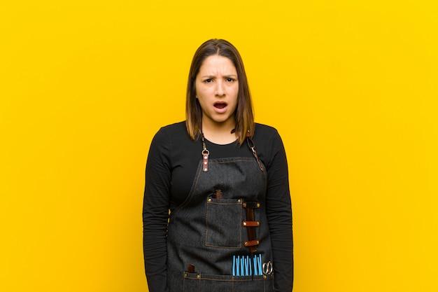 Friseurfrau, die entsetzt, verärgert, gestört oder enttäuscht, mit offenem mund und wütend gegen orange schaut