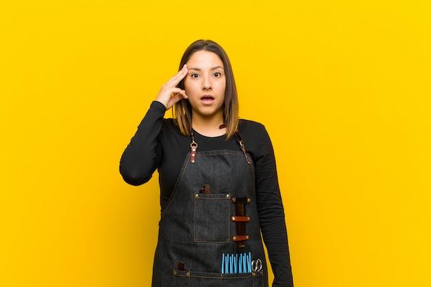 Friseurfrau, die überrascht, mit offenem mund, entsetzt schaut und einen neuen gedanken, eine idee oder ein konzept gegen orange verwirklicht