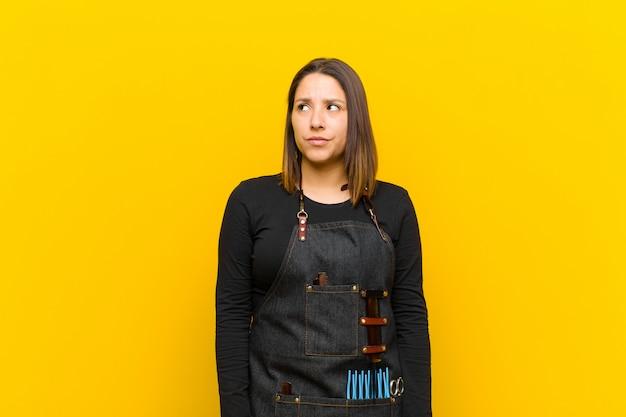 Friseurfrau, die verwirrt und verwirrt schaut, ein problem wundert oder versucht zu lösen oder gegen orange hintergrund denkt