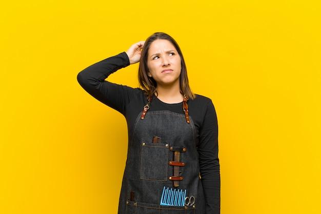 Friseurfrau, die verwirrt und verwirrt sich fühlt, kopf verkratzend und zur seite schauend