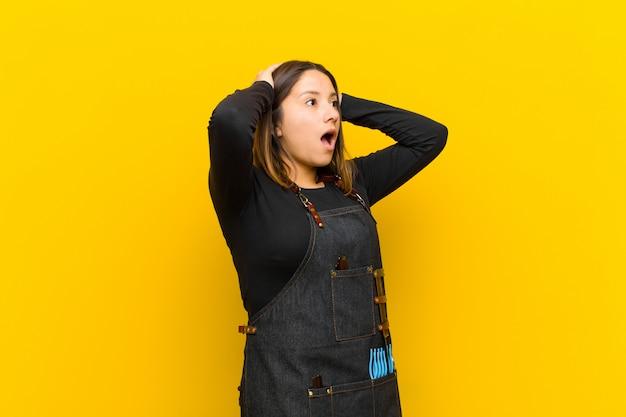 Friseurfrau mit offenem mund, schauend entsetzt und entsetzt wegen eines schrecklichen fehlers und heben hände an, um gegen orange hintergrund voranzugehen