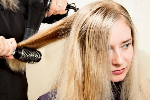 Friseurhände, die langes blondes haar trocknen