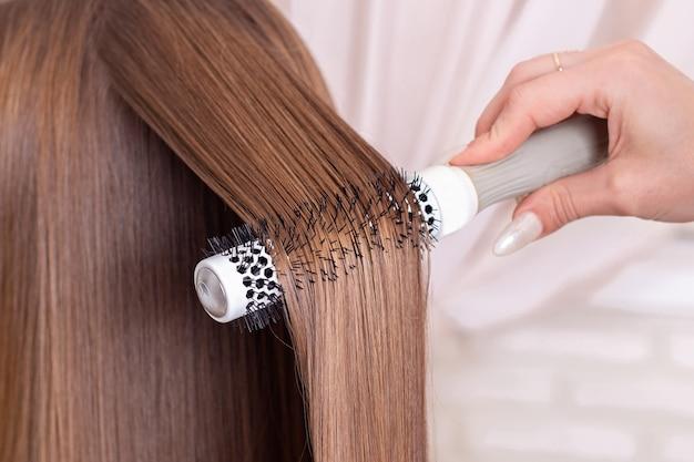 Friseurhand, die haare bürstet