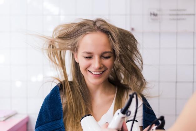 Friseurin der jungen frau mit einem fön in seinen händen frisur frau schönheitshaar professioneller schönheitssalon