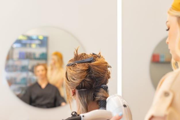 Friseurin, die mit kunden in salonansicht von hinten haartrocknen und styling-ansicht von b...
