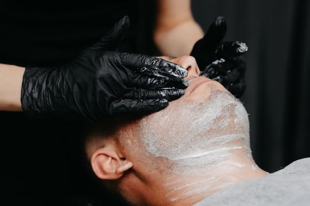 Friseurin, die rasierschaum anwendet, bevor sie sich mit einem rasiermesser rasiert.