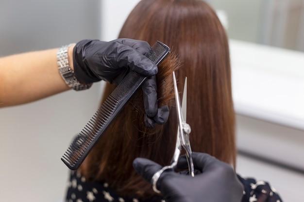 Friseurin macht einen haarschnitt. professionelle friseurwerkzeuge, ausrüstung.