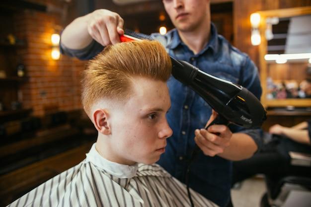 Friseurjungenhaarschnitt-friseur im friseurladen. modische stilvolle retro-frisur. porträt eines kindes mit einem schönen haarschnitt.