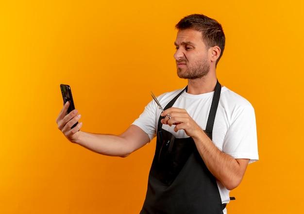 Friseurmann in der schürze, der bildschirm seines handys betrachtet, der schere hält, die unzufrieden steht und über orange wand steht