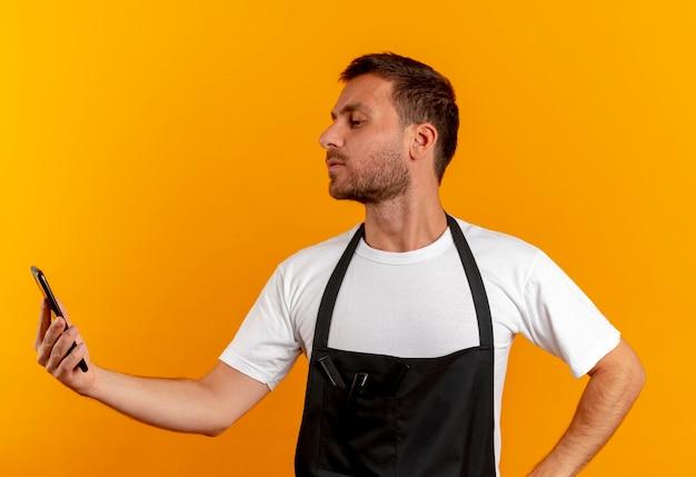 Friseurmann in der schürze, der bildschirm seines handys mit ernstem gesicht betrachtet, das über orange wand steht