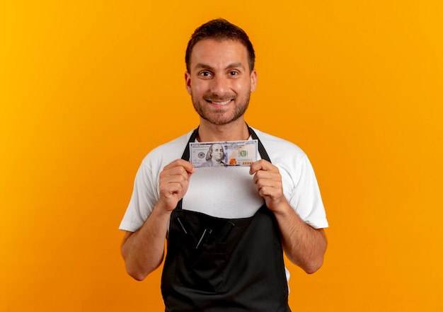 Friseurmann in der schürze, die bargeld hält, das nach vorne mit lächeln auf gesicht steht, das über orange wand steht