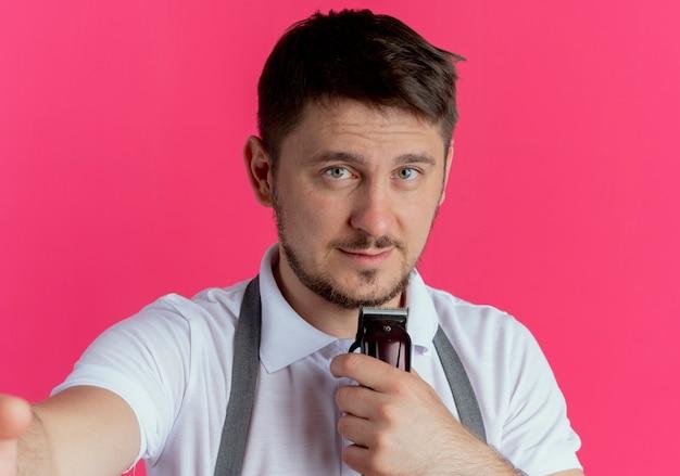 Friseurmann in der schürze, die bartschneider hält, der kamera mit lächeln auf gesicht betrachtet, das über rosa hintergrund steht