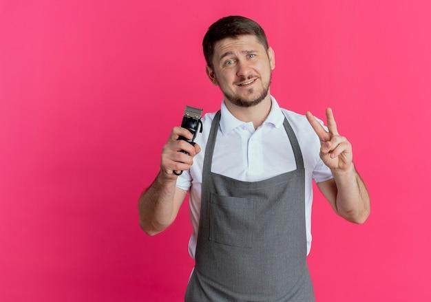 Friseurmann in der schürze, die bartschneider hält, der siegeszeichen zeigt kamera mit lächeln auf gesicht steht über rosa hintergrund