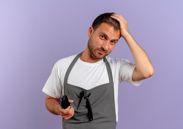 Friseurmann in der schürze, die haarbürste hält, die nach vorne mit sicherem ausdruck steht, der über lila wand steht