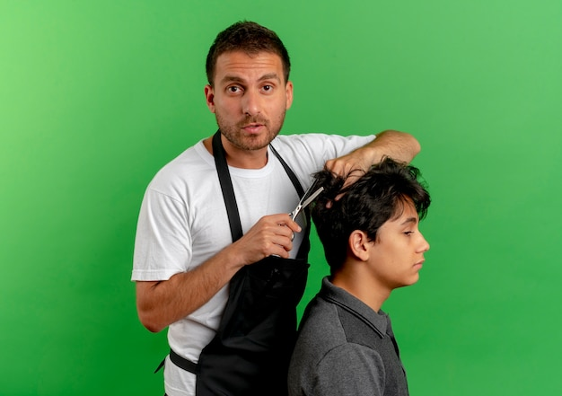 Friseurmann in der schürze, die haare mit der schere des zufriedenen kunden schneidet, der über grüner wand steht