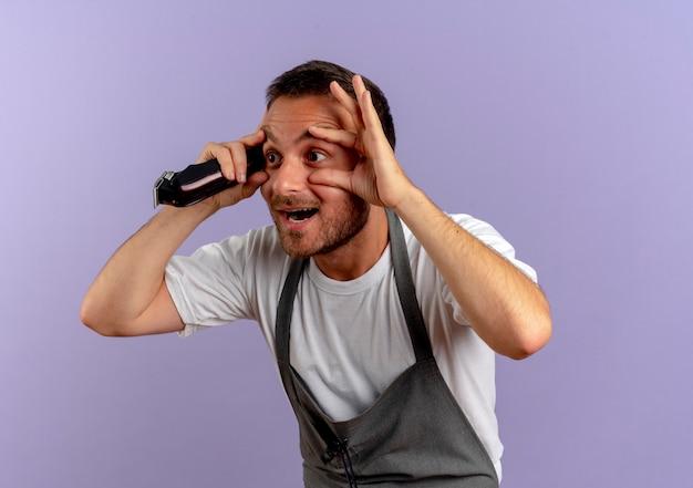 Friseurmann in der schürze, die haarschneidemaschine hält, die augen mit den fingern öffnet, die versuchen zu sehen, über lila wand zu stehen