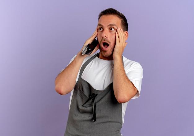 Friseurmann in der schürze, die haarschneidemaschine hält, die beiseite geschockt mit weit geöffnetem mund steht, der über lila wand steht