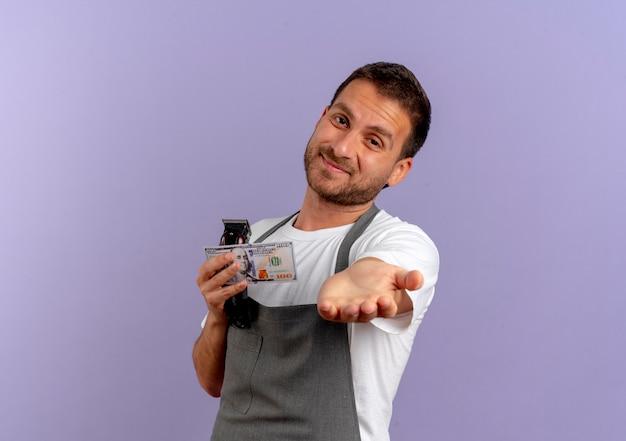 Friseurmann in der schürze, die haarschneidemaschine hält hand vor sich hält und um geld bittet, das über lila wand steht
