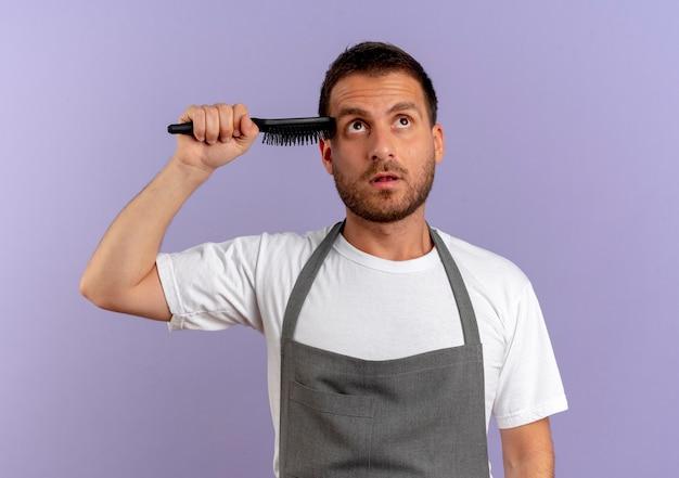 Friseurmann in der schürze, die haarschneidemaschine und haarbürste hält, die über lila wand stehen