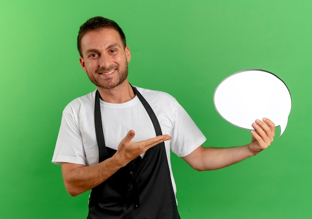 Friseurmann in der schürze, die leeres sprachblasenzeichen hält, das es mit arm seiner hand darstellt, die über grüner wand steht