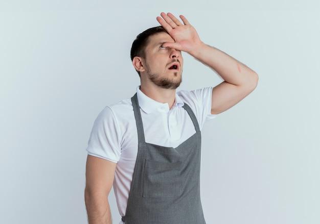 Friseurmann in der schürze, die müde und gelangweilt mit hand über kopf rollende augen hoch steht über weißem hintergrund
