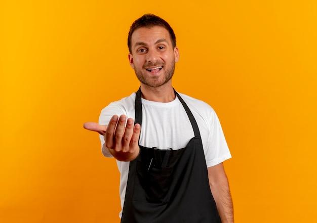 Friseurmann in der schürze, die nach vorne schaut und einlädt, mit lächelnder freundlicher hand hereinzukommen, die über orange wand steht