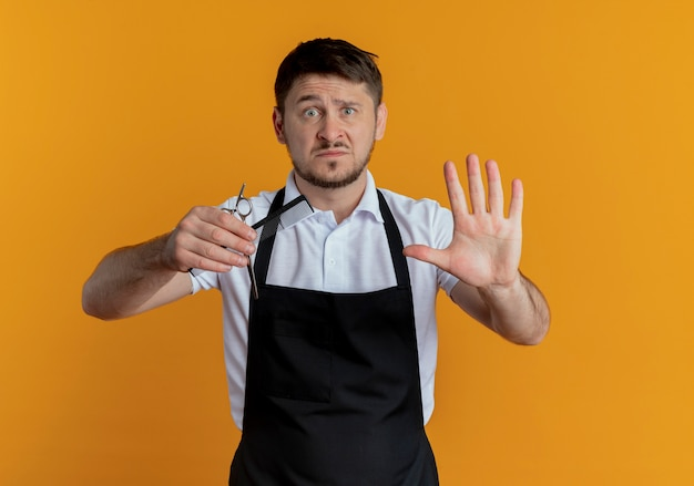 Friseurmann in der schürze, die schere und kamm hält, die aufhören, mit offener hand zu singen, die kamera mit ernstem gesicht betrachtet, das über orange hintergrund steht