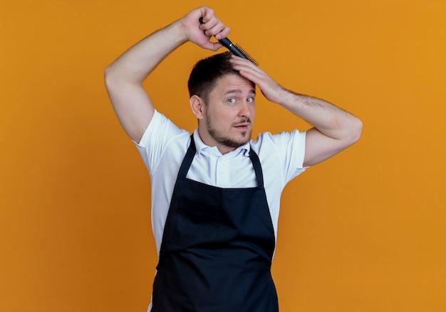 Friseurmann in der schürze, die sein haar kämmend aussehend steht und über orange hintergrund steht