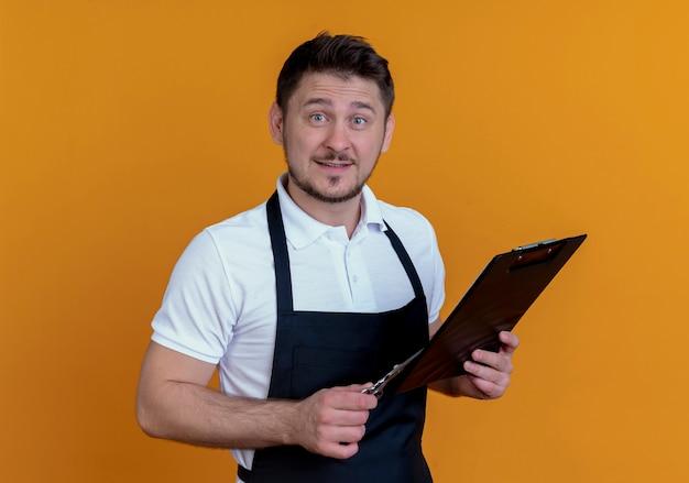 Friseurmann in der schürze, die zwischenablage und schere hält, die kamera mit lächeln auf gesicht betrachtet, das über orange hintergrund steht