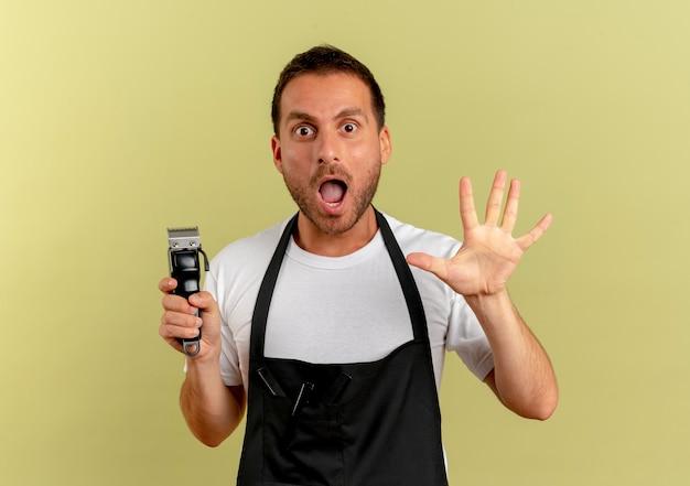 Friseurmann in der schürze hält haarschneidemaschine, die nach vorne schaut, überrascht mit offener erhabener hand, die über lichtwand steht