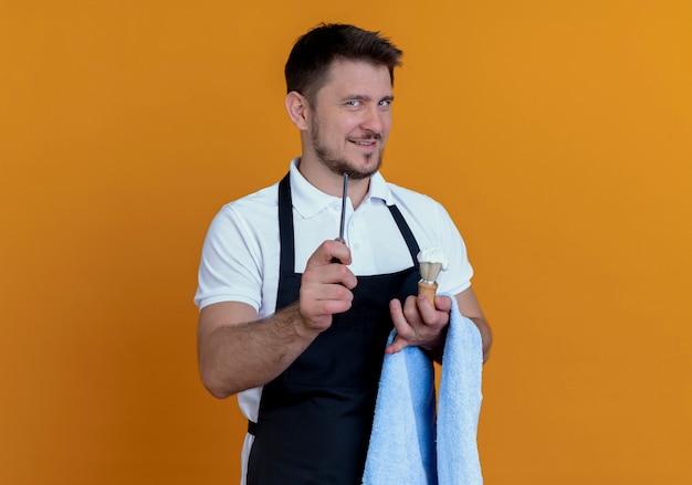 Friseurmann in der schürze mit handtuch auf seiner hand, die rasierpinsel mit schaum und rasiermesser hält und kamera betrachtet, die zuversichtlich steht, über orange hintergrund zu stehen