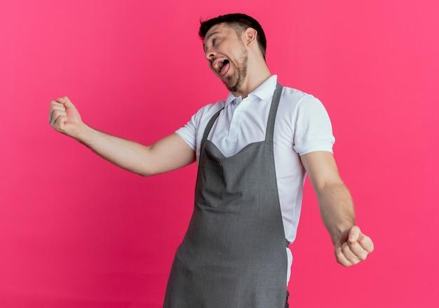 Friseurmann in der schürze verrückt glücklich, spaß zu haben, zunge herauszustehen, die über rosa hintergrund steht