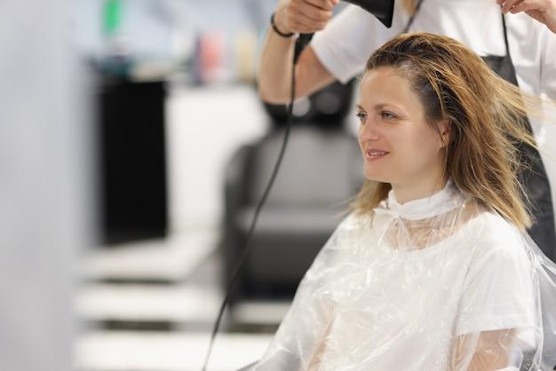 Friseurmeister trocknet haare mit fön an kunden im schönheitssalon