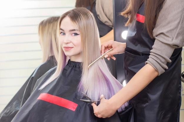 Friseursalon. der friseur schneidet einem mädchen mit einer schere die haare. mädchen in einem schönheitssalon, haarpflege