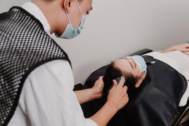 Friseursalon-konzept ein männlicher friseur, der eine wasserdusche hält und sanft die haare einer weiblichen kundin wäscht.