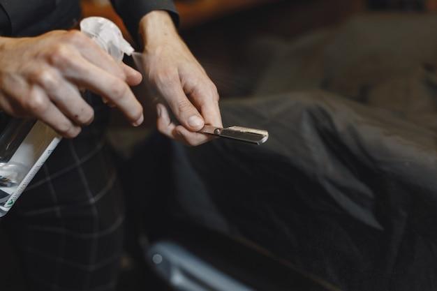 Friseursalon. nahaufnahme des friseurs hält rasiermesser für das rasieren seines bartes
