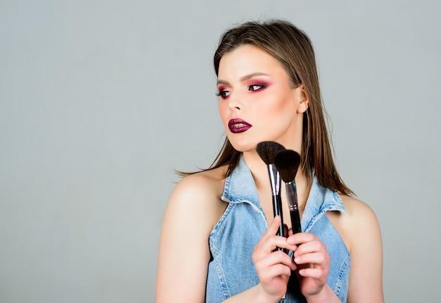 Friseursalon schönheit. lippenstift und lidschatten. sinnliche frau mit langen haaren, stil. sexualität. kosmetik für die hautpflege. mode-make-up-gesicht. sexy frau mit professionellem make-up-pinsel. platz kopieren.