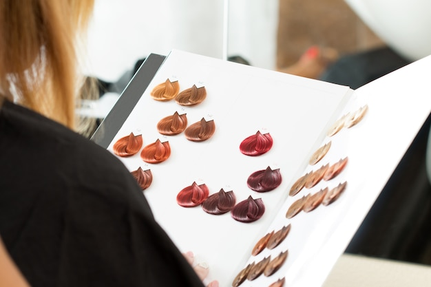 Friseursalonbesucher, der das buch der farbmuster nah betrachtet. besucher, der am friseurbüro sitzt, das neue haarfarbe wählt. haarpflege, kosmetikerin, färben oder ändern des haarfarbenkonzepts Premium Fotos