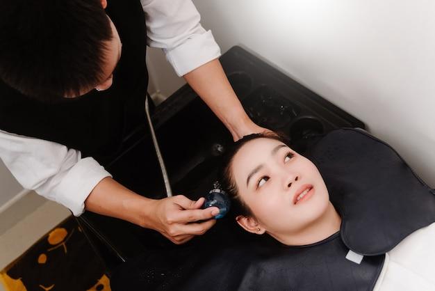 Friseursalonkonzept ein männlicher friseur, der eine wasserdusche hält, die das haar einer kundin sanft wäscht.