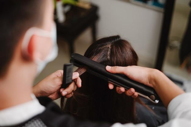 Friseursalonkonzept ein männlicher friseur, der mit einem haarglätter arbeitet, um die haare einer weiblichen kundin zu glätten.