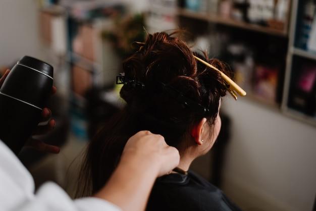 Friseursalonkonzept ein männlicher friseur, der mit einem kamm eine haarlocke greift und einen haartrockner zum trocknen und glätten verwendet
