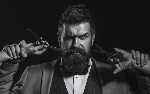 Friseurschere und rasiermesser, friseurladen. herrenhaarschnitt, rasieren. bärtiger mann, langer bart, brutaler, kaukasischer hipster mit schnurrbart