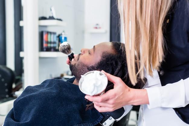 Friseurseifenkunde, der sich bereit macht, ihn zu rasieren