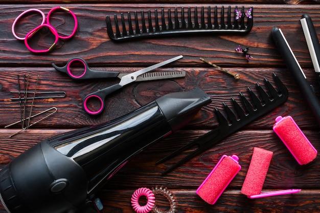 Friseurset, lockenwickler, haargummis auf dem hölzernen hintergrund
