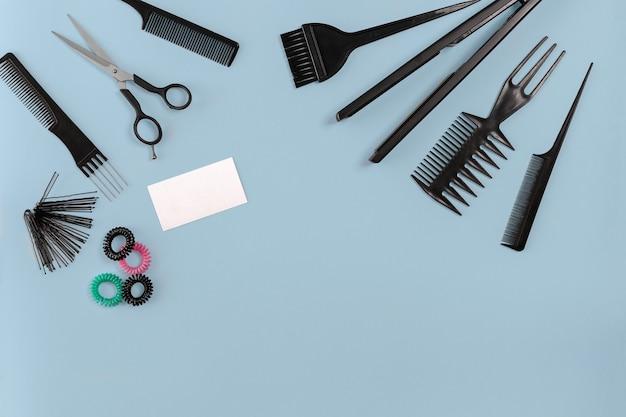 Friseurwerkzeuge auf blauem hintergrund mit kopienraum, draufsicht, flache lage. kamm, schere, effilierschere, haarspange. stillleben.