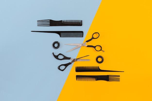 Friseurwerkzeuge auf blauem und gelbem hintergrund mit kopienraum draufsicht flach