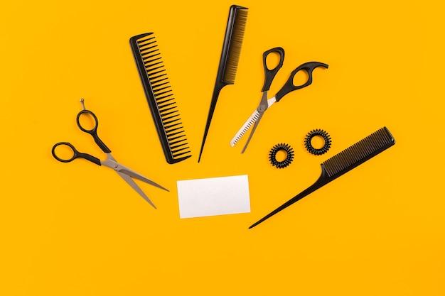 Friseurwerkzeuge auf gelbem hintergrund mit kopienraum, draufsicht, flache lage. kamm, schere, effilierschere, haarspange. stillleben.